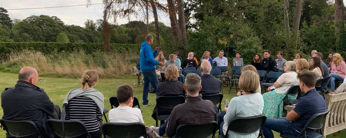 Simon guillebaud speaks to a group of people sat in a garden in the UK