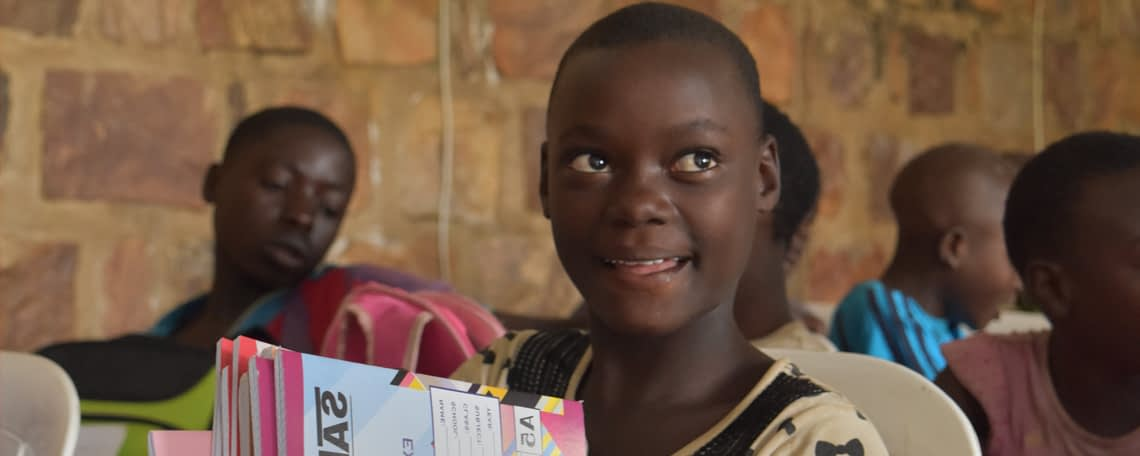 a girl smiles as she is given school materials