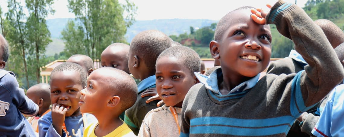 Burundian Schoolchildren outside gathered and smiling, looking in all directions