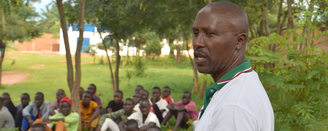 Ephraim speaks outdoors to a group of young men