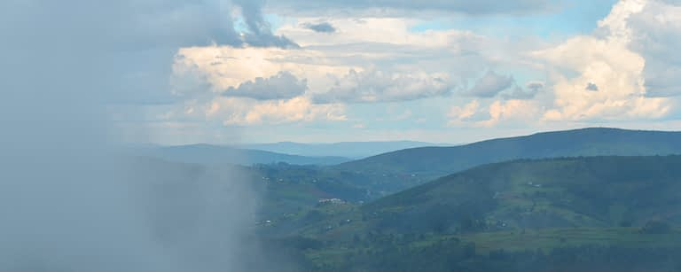 peaceful green Burundi hills with clouds and fog as the sun shines through