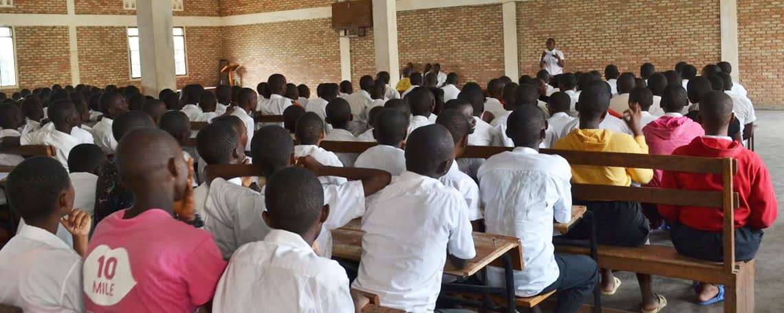 students in white shirts sit on benches listening to a lecture