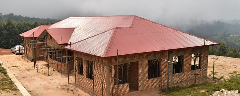 a nearly-completed building with a red roof and with scaffolding atop a hill