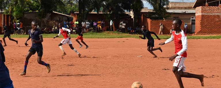 Boys playing a football match on a red dirt pitch