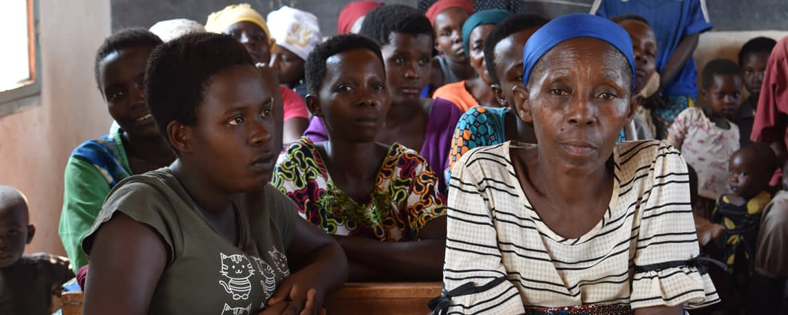 A group of women in a classroom are listening, one woman looks directly at the camera