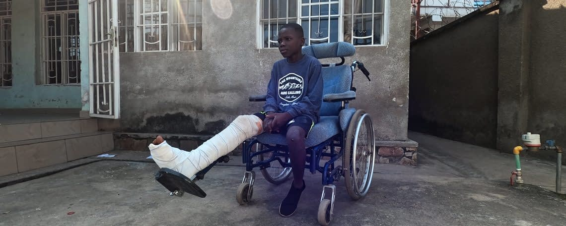 Issa sits in his wheelchair with a broken leg-new generation Burundi