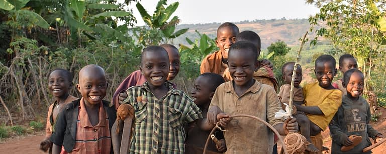 a group of Children pose and smile for the camera in the evening light, one holds a hoop