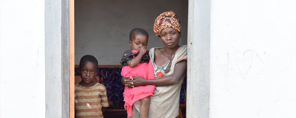 a woman holding a baby stand in the doorway of a new home with her son next to her