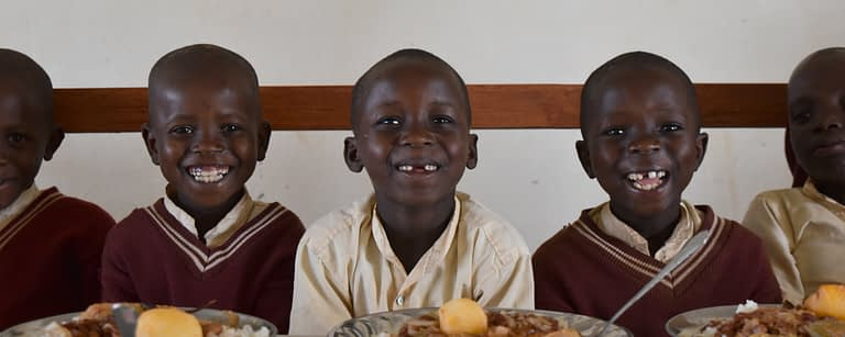 School Children sit smiling waiting to eat plates of food