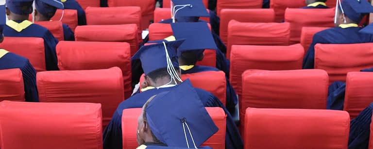 socially-distanced graduates of antioch school in caps and gowns