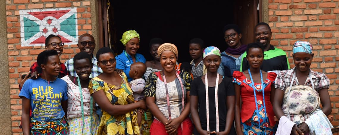 the ladies of the sewing class smile together outside their classroom