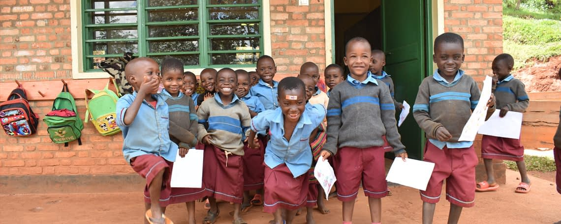 A group of schoolchildren in uniform smile and laugh together outside their classroom