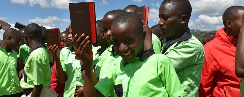 a schoolgirl holds up her new bible smiling