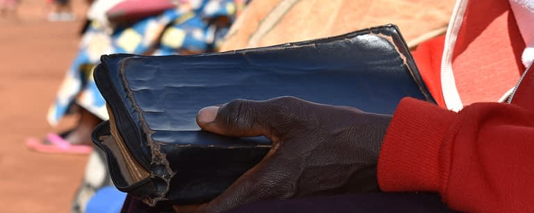 Close up of a bible held by a woman