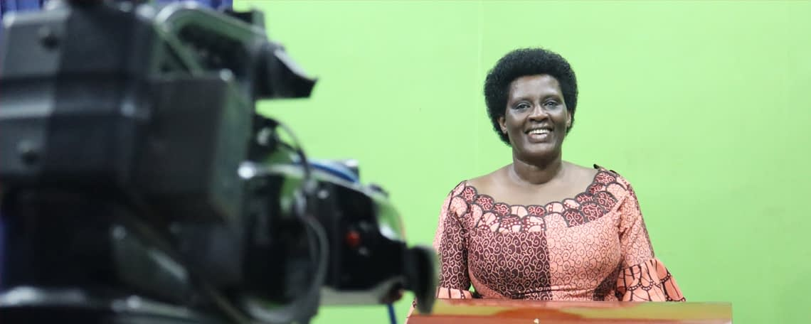 a woman stands at a lectern in front of a greenscree, a camera is focused on her