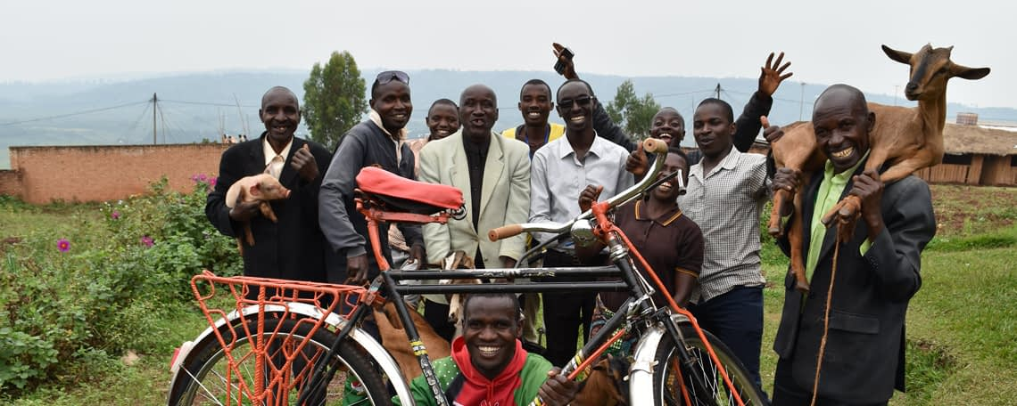a group of people smile and hold up their alternative gifts of a goat, a bike, a pig etc