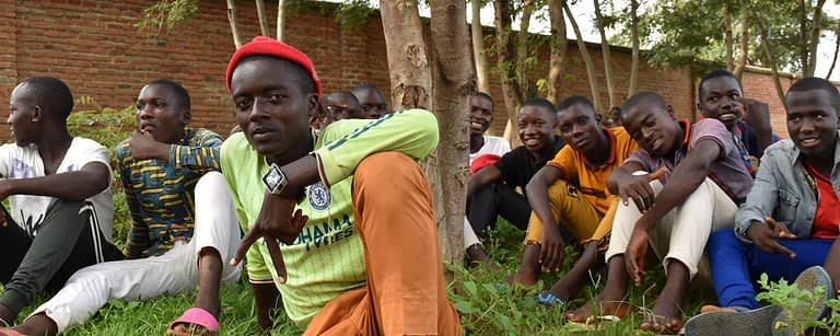 a group of teenage boys pose and smile for a photo whilst sat by trees