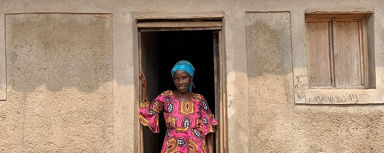 a woman stands in the doorway of her new house