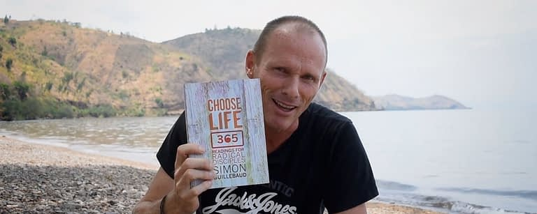 simon holds up the choose life 365 book by a lake