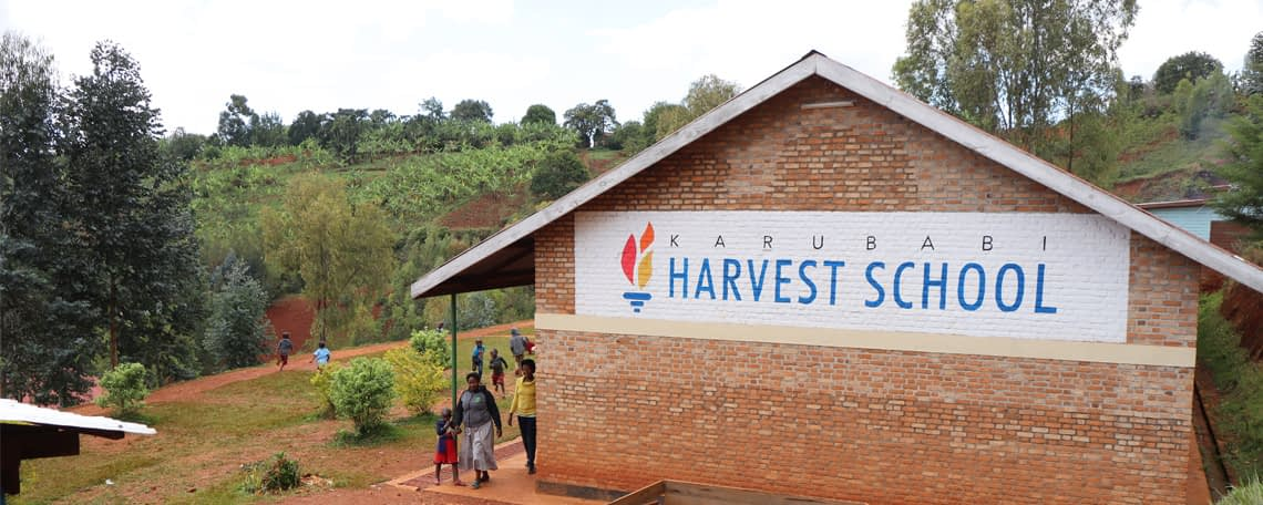 a view of a school building in the hills. The wall of the building says Karubabi Harvest School